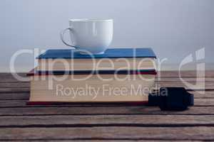 Books with cup of coffee and smart watch on wooden table