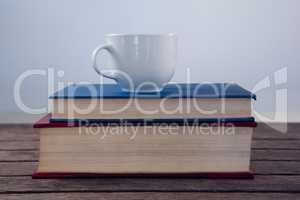 Books with cup of coffee on wooden table