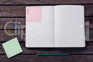Diary, sticky notes, pencil and paper clip on wooden table