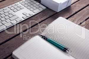 Keyboard, diary, pen and box on wooden table