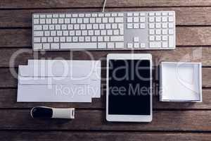 Keyboard, digital tablet, envelope, box and stapler on wooden table