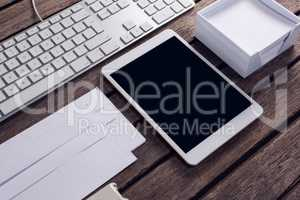 Keyboard, digital tablet, envelope and box on wooden table