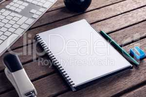 Keyboard, diary, stationery and stapler on wooden table