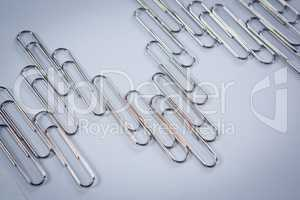 Paper clips arranged on white background