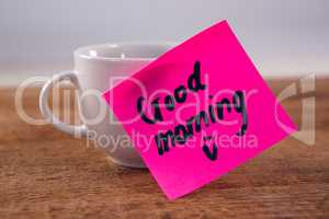 Black coffee with message on wooden plank