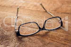 Spectacles on wooden table