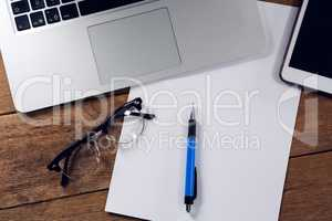 Digital tablet, laptop, paper, pen and spectacles on wooden table