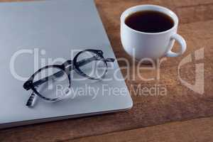 Spectacles on laptop with black coffee at desk
