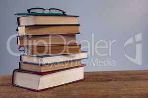 Spectacles and pencil on book stack