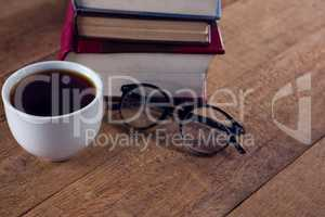 Spectacles, black coffee and book stack on wooden table