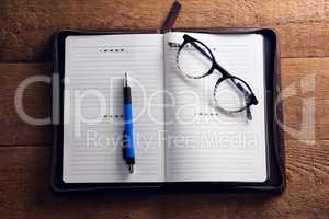 Spectacles and pen on organizer at desk
