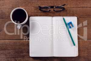 Book, pencil, sharpener, spectacles and black coffee on wooden table