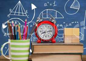 Objects on Desk foreground with blackboard graphics of math equations