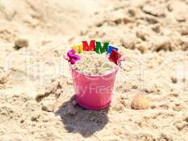 Pink baby bucket with sand and inscription summer