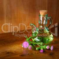 Oil and flowers of milk thistle on wooden