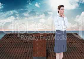 Businesswoman standing on Roof with chimney and ocean landscape