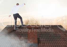 Businessman standing on Roof with chimney and trees in evening light