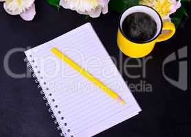 paper notebook with a yellow wooden pencil
