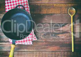 empty black cast-iron frying pan and wooden spoon