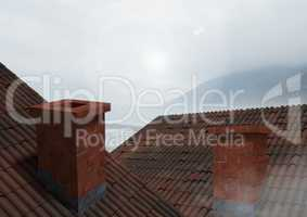 Roofs with chimney and cloudy mountains