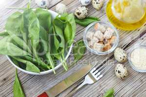 Healthy breakfast. Fresh baby spinach leaves. Ingredients for spinach salad with quail eggs