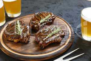 Very delicious steak BBQ and beer in glasses on a black stone background