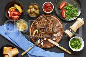 Appetizing barbecue steak at the dinner table in a restaurant with fresh vegetables, olives and wine. Italian Tradition