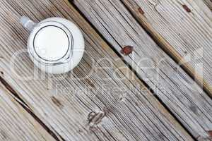Natural food. A jug of cow milk on a wooden table, top view, closeup. Rustic style.