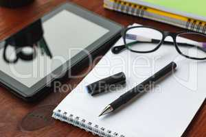 The concept: the beginning of work. Pen, open notebook, tablet computer and glasses on office desk.