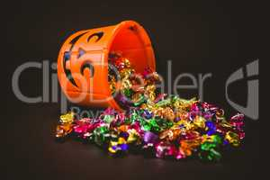 Bucket with chocolates during Halloween over black background