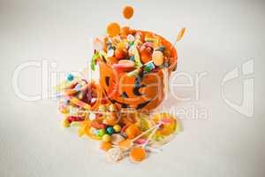 View of orange bucket with various sweet food during Halloween