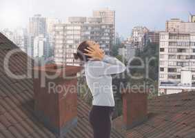 Businesswoman standing on Roofs with chimney contrasting with apartment blocks