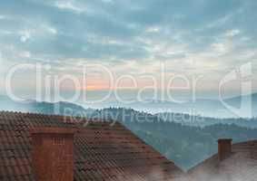 Roofs with chimney and misty landscape