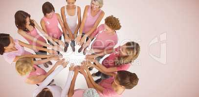 Composite image of female friends supporting breast cancer awareness