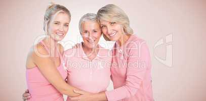 Composite image of portrait of smiling daughters with mother supporting breast cancer awareness