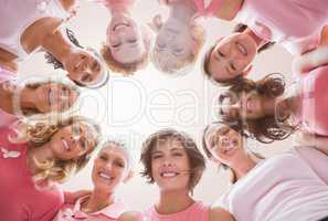 Composite image of low angle portrait of female friends supporting breast cancer