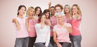 Composite image of portrait of female friends showing thums up sign for breast cancer awareness