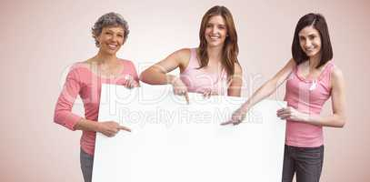 Composite image of women in pink outfits holding board for breast cancer awareness