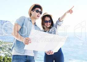 Millennial couple with map against blurry coastline