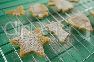 Powdered sugar on cookies over cooling rack