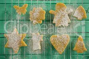 Directly above shot of powdered sugar on cookies over cooling rack