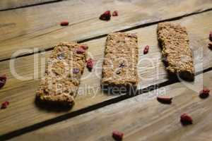 Three granola bars arranged on wooden table