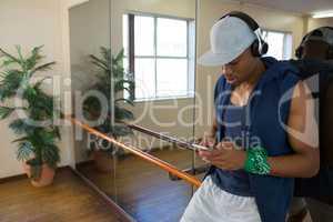 Male dancer using phone in studio
