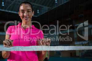 Portrait of female volleyball player behind net