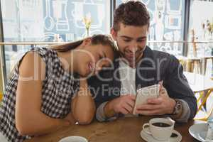 Man with woman using phone in cafe