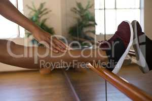 Low section of dancer stretching leg on barre