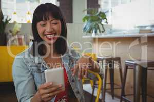 Happy woman using phone at cafe
