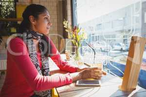 Thoughtful woman with drink at window sill in cafe