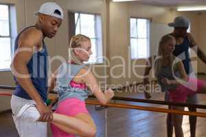 Man assisting female friend in stretching leg on barre