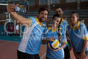 Male volleyball player with team taking selfie